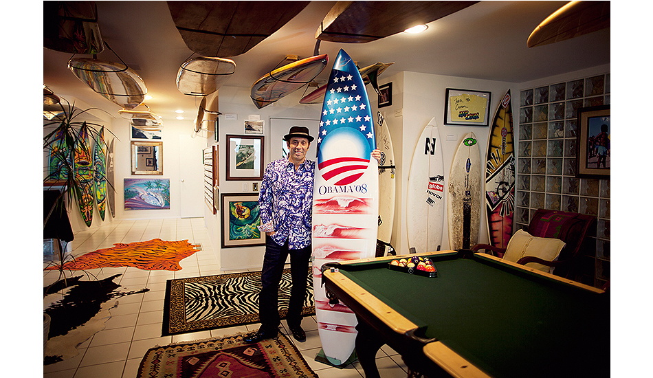 """A SURFER'S DREAM HOME. Fernando Aguerre was one of the founders of Reef Sandals – which he and his brother Santiago founded in 1984. Twenty years of 12-14 hour work days later, they sold Reef to Vanity Fair Corporation. Originally from Argentina, Fernando came to America with big schemes and dreams, and now lives in a surfer's dream home - a cozy beach shack on La Jolla's """"Street of Dreams."""" Big Rock and Windansea are visible off to the right, and there's a whole lot of Pacific Ocean reflecting off the white walls of his home which is filled with surf art from around the world. Within Fernando's house is a beautiful, tasteful tribute to Che Guevara, surf culture, soccer, family and other things that appeal to Fernando's iconoclastic view of the world. He also has a dreamy collection of surfboards – from original and re-created olo and alaia to modern thrusters from the likes of Kelly Slater, Rob Machado, Rochelle Ballard and Andy Irons. In 2008, Fernando had a bro-down with everyone's favorite styling bodysurfer – President Barack Obama. Fernando has a photo of Obama signing his """"Obama Surfs"""" t-shirt, and he also has this one-of-a-kind board intended for the president's first election campaign. Fernando explained: """"The board was shaped by Rusty, a long-time Republican, who decided to support then-Senator Obama's presidential bid. The fundraising committee could not take 'in kind donations,' so Rusty was stuck with a very nice board, shaped by him, and painted by a famous NASCAR race car painter from San Diego. Incredible art, with the flag stripes being peeling waves and the same artwork on the other side of the board. The board sat at Rusty's for a few weeks until I found out about it. I offered to buy it, we agreed on the price, Rusty got the money then donated it to the Obama campaign. And I got one of the rarest and most unusual boards in history, the one and only 'Obama surfboard by Rusty.'"""" Photo: Lucia Griggi/Lensbaby."""