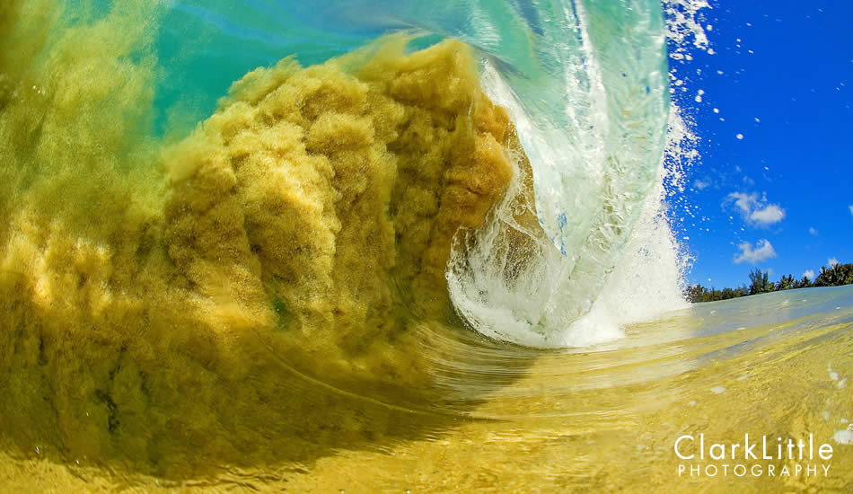 """I am standing in knee-deep water as this wave heaves up and over. It is so shallow that the sand is getting sucked into the wave. The sun is directly overhead at noon, which lights up the sand. Photo: <a href=\""""http://ClarkLittlePhotography.com\"""" target=_blank>Clark Little</a>."""