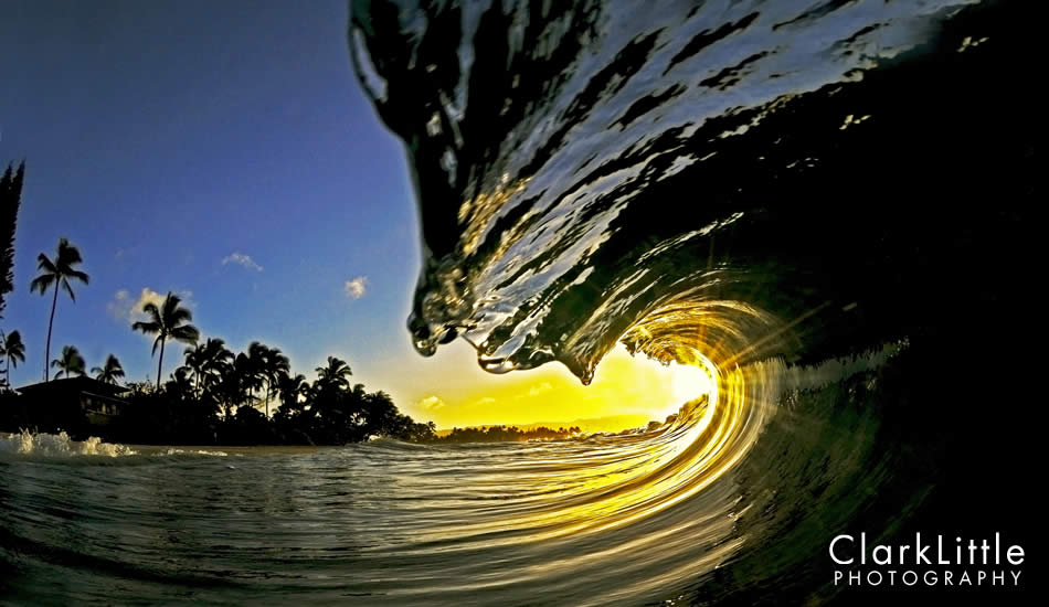 """The silhouette of palm trees and a wave frames the setting sun. Photo: <a href=\""""http://ClarkLittlePhotography.com\"""" target=_blank>Clark Little</a>."""