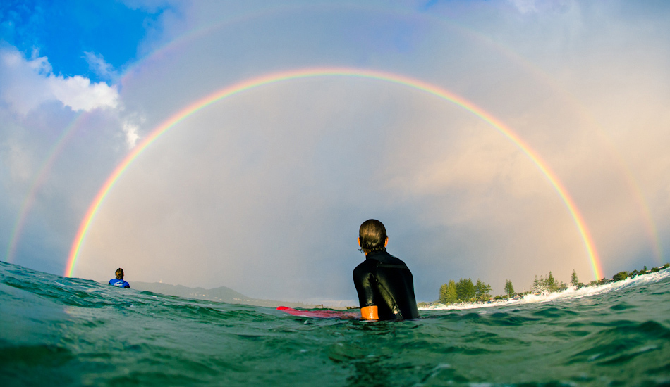 "Joe Guinand sitting in awe under the most ridiculous double rainbow spanning across the Bay. Image: <a href=""http://www.alexfrings.com\"" target=\""_blank\"">Frings</a>"