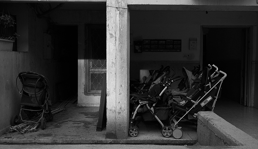 Baby strollers in the entrance of Meir\'s building. In the Jewish orthodox society, it is a blessing to have many children.