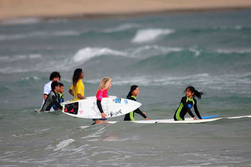 Wanning youth go for a surf with a couple of competitors. Photo: ISA/Tweddle