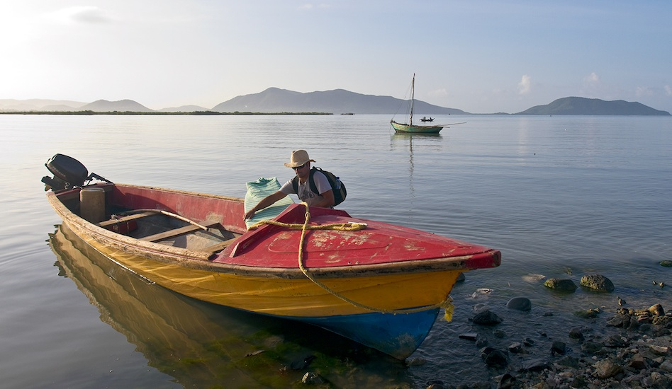 Early morning calm in Aquin as Emiliano Cataldi loads boards for a boat trip to distant Caribbean reefs.  Photo: John Seaton Callahan.