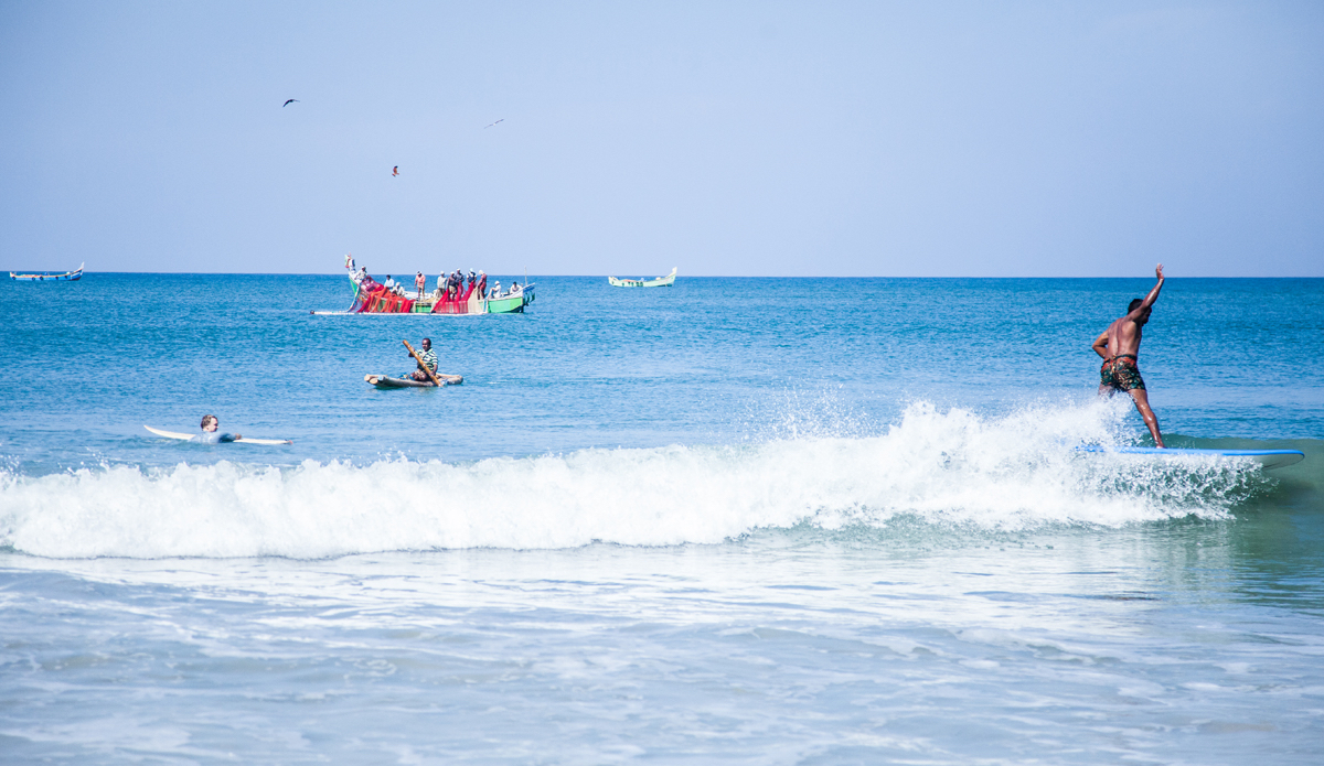 """Mujeeb is surfing the board he bought from one of the travellers. He also started to rent boards to earn some money. Mujeeb is wearing traditional Indian lungi instead of board shorts. Photo: <a href=\""""http://www.Godoberta.com\"""">GodoBerta.com</a>"""