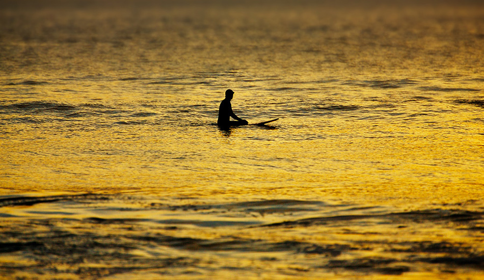 "A lonely surfer waits for \'One More Wave\' during a warm golden sunset at Gwithian beach in Cornwall. Photo: <a href=""http://www.jordanweeks.com/\"" target=_blank>Jordan Weeks</a>"