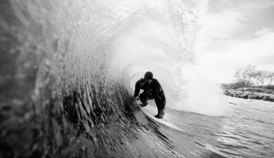"""A cold stormy day breaking right on the rocks, Kelly prepares for the next hollow section to spit him out into the channel. Photo: <a href=\""""http://www.lowtiderising.com/\"""" target=\""""_blank\"""">Aroyan</a>"""
