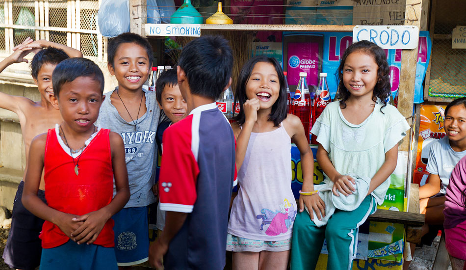 Local children at a sari-sari shop, with gasoline for motorbikes sold by the liter from Coke and Pepsi bottles. Photo: Callahan/SurfExplore