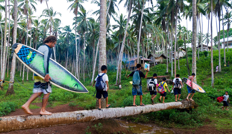All the kids came out from the village to watch, escorting Erwan and Phil across the coconut-log bridge and back up the track. Photo: Callahan/SurfExplore