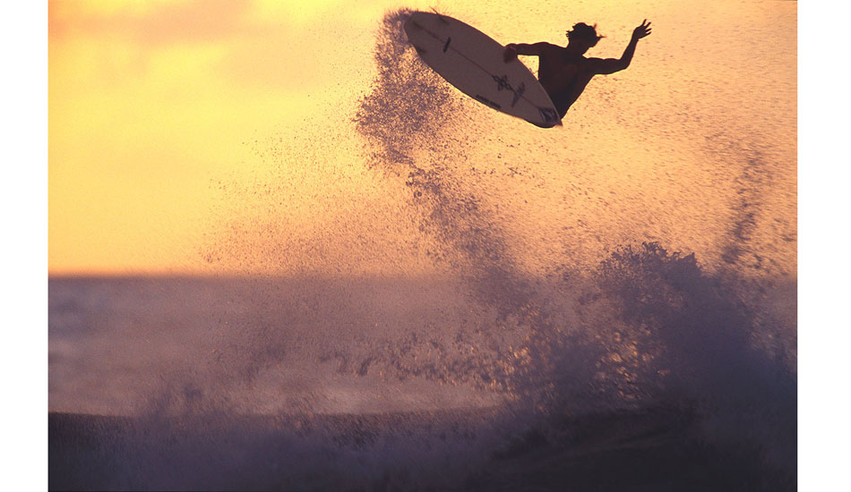 "This was maybe 1999, and it was super late in the day. Heaps of photog\'s had packed up and left for the day, and there were only a few left on the beach at Off The Wall. I saw the golden light starting to build in the sky, so I headed down towards Backdoor on the off chance that if Bruce busted an air, he might do it against this one golden bit of sky, thus at least giving me a backlit silhouette of him. Sure enough, Bruce goes huge, and I took about six slides of it at at about a 40th or a second. Here\'s the amazing bit: during just that moment of inertia at the height of his maneuver, he was still enough for me to produce a reasonably sharp image. None of the others were anywhere near as good. Photo: <a href=""http://seandavey.com//\"" target=_blank>Sean Davey</a>"