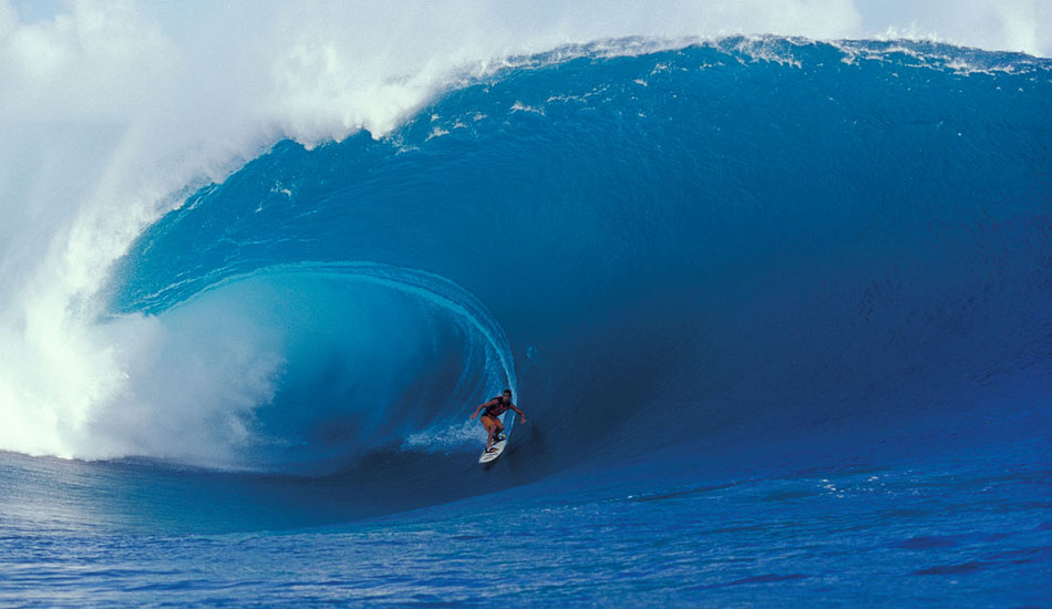 "At the time, this was the biggest wave ever surfed there, and it caused quite a stir in the magazines.  What was really rad about this photo for me was that we were in a tiny little dinghy, five of us (four photog\'s and one driver). Our driver was a local surfer, very familiar with the reef at Teahupoo. He was very confident and would often have us sitting some 30 or 40 feet closer to the action than the other boats. This continually unnerved me. Then this thing came through, and I looked up at it thinking, ""we are done. There is absolutely nothing that I can do, so I will simply shoot it,\"" just on the off chance that we somehow make it out of this situation. It was that serious. Scared the crap out of me, but I did get the shot. Kissed the ground when I stepped off the boat that afternoon. Moral of this story was always shoot if you can, even if it means going down in a blaze of glory, which thankfully, we didn\'t on this occasion...
