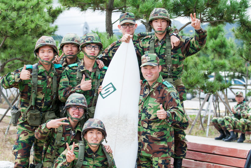 """Some young ROK soldiers break the hardship and monotony of their compulsory two year military service defending Korea and grab a chance to pose with my surfboard during a military exercise and a pumping NE swell. I wonder if any of these guys know what a thruster is? Photo: <a href=\""""http://www.shannonaston.com/\"""" target=_blank>Shannon Aston</a>."""