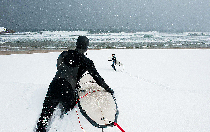 """Korean surfers, Moonjun Bae and Young-ik Son, clamber over huge snowdrifts to get out there for a couple of chilly peaks. Photo: <a href=\""""http://www.shannonaston.com/\"""" target=_blank>Shannon Aston</a>."""