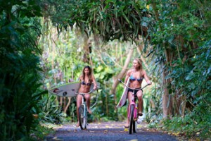 Surfer girls, Nikki Van Dijk and friend on bikes in Hawaii.