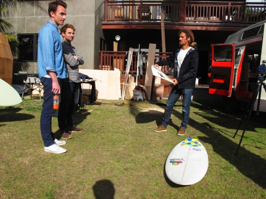 Director Tyler Manson, artist Jay Nelson, and Rob Machado prepare for a surf break.