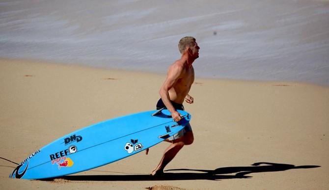 Mick Fanning drops his board to run to Evan Geislman's rescue. Photo: Matt Hoffman/Gnarbox