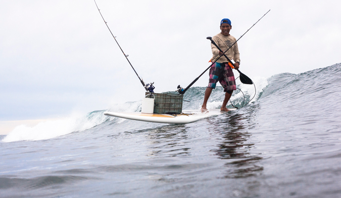 Local fishing and surfing legend, Marco Lupiano, rides one in with the day's catch! Photo Courtesy of Two Feet and Classy