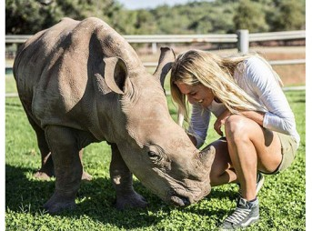 Stephanie Gilmore with a baby rhino whose mother was killed by assholes so other assholes can buy horns.
