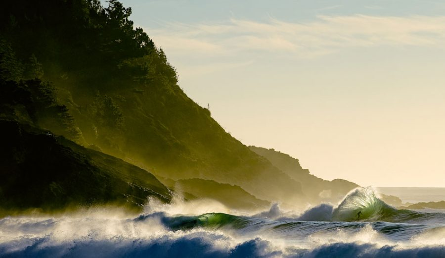 """This shot, taken by Chris Burkard, actually won a Red Bull Illume contest for all categories as well as the """"Illumination"""" category. The shorebreak was so big and the offshore plumes so high this day, that I missed most of the best waves, but finally a set came through. The light, the wind, and the swell were perfect. It was as if everything in nature fell into perfect harmony for this single moment. As Peter Mendia eased into this wave, the backwash hit, sending a golden shower of water 10-feet above his head, and sending him down the line of another 20-second barrel. Photo: BurkardPhoto.com"""