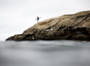 A surfer in Santa Cruz about to transition from thinking about surfing to the act of surfing. Photo: Sean Ruttkay
