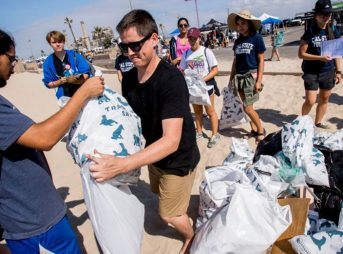Andrew Sneddon, center, of Coastal Playground, accepts trash collected by volunteers during the California Coastal Cleanup Day at Huntington State Beach on Saturday, September 16, 2017.