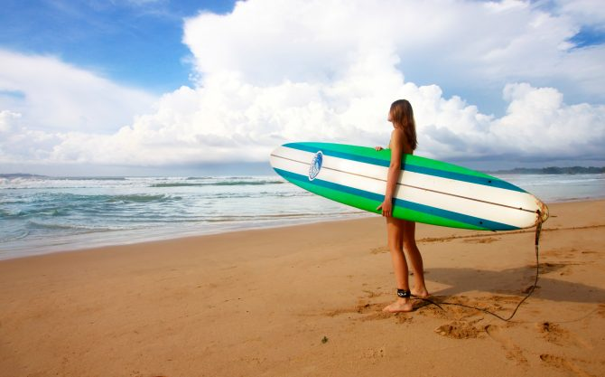 Woman Standing with Surfboard at Ocean
