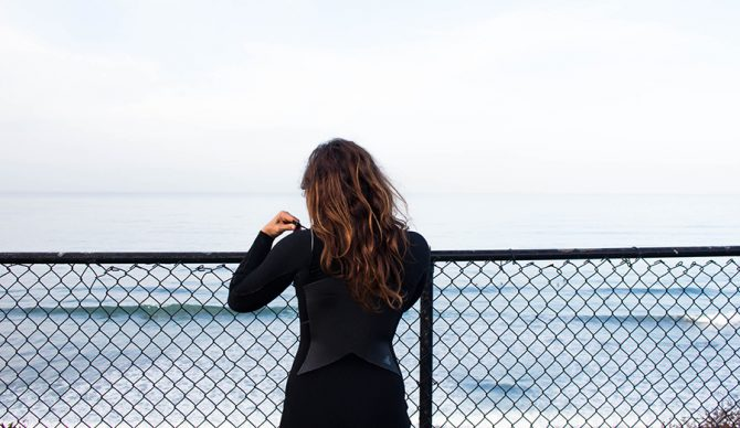 A woman looks at the ocean while wearing a wetsuit